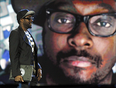 Recording artist Will.i.am walks past an oversized image of himself as he arrives on stage during an Intel keynote address at the 2012 International Consumer Electronics Show.