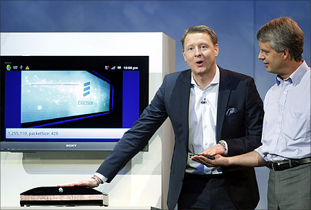Hans Vestberg (L), president and chief executive of the Ericsson Group, transfers a photo from a smartphone to a computer screen using his body.