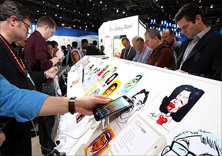 Showgoers look over the Samsung Galaxy Note phone/tablet.