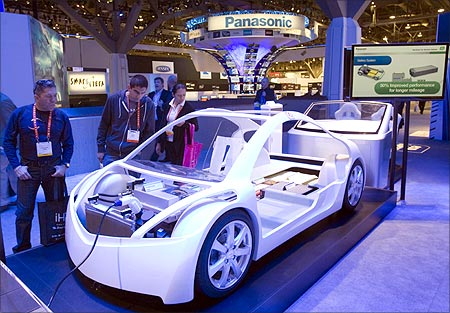 Visitors check a display at the Panasonic booth showing electric vehicle technology.