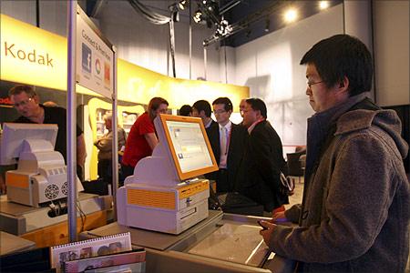 Yi Ding of Los Angeles uses a Kodak photo kiosk.