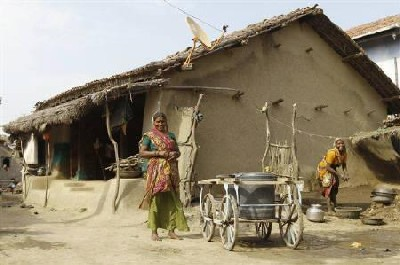 Villagers smile outside their mud house in Khun village near Dholera town in Gujarat.