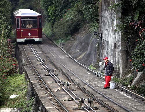 A worker stands next to a track as a tram approaches on its way up The Peak in Hong Kong.