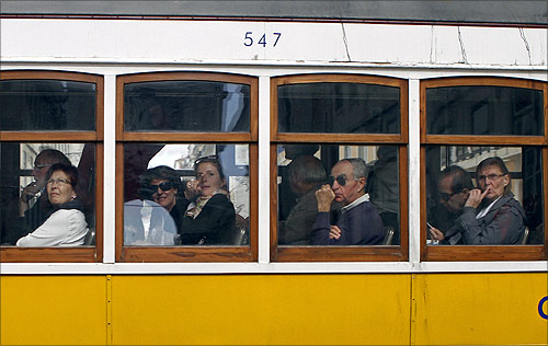 Passengers look outside from a tram in Lisbon.