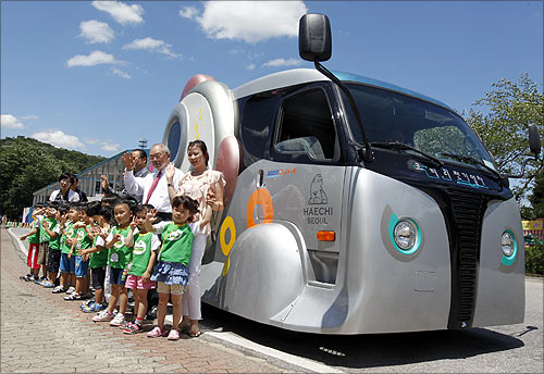 People pose in front of a wireless electric tram during its launch ceremony at Seoul Grand Park in Gwacheon, south of Seoul.