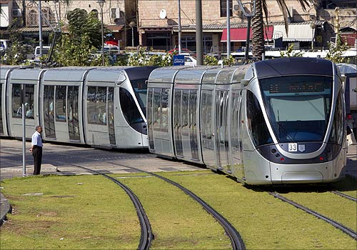 A pedestrian looks as a light rail tram passes by in Jerusalem.
