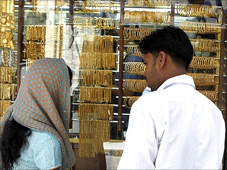 Customers look at gold in a jewellery shop in Amman.