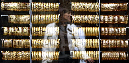 A woman is reflected on the window of a jewellery shop.