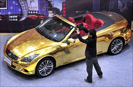 A man films a gold-plated Infiniti G37 at a jewelry store in Nanjing, Jiangsu province.