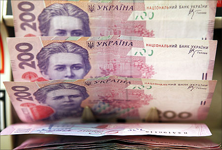 A cashier counts Ukrainian hryvnia banknotes at a shop in Kiev.