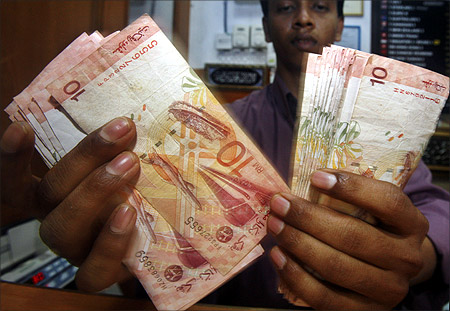 A money changer shows Malaysian ringgit notes at his shop in Putrajaya.