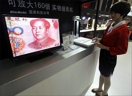 An employee operates a camera to zoom in on the image of a Chinese one-hundred yuan banknote at a production exhibition in Wuhan.