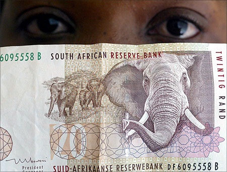 A bank teller looks at South African rand note.