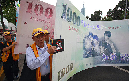 Protesters carry a banner printed with the new Taiwan dollar currency.