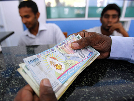 A customer holds Sri Lankan rupee notes as he waits for more cash from a teller at a money exchange in Colombo.