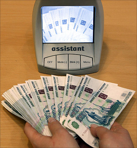 An employee of a bank checks the authenticity of Russian rouble banknotes.