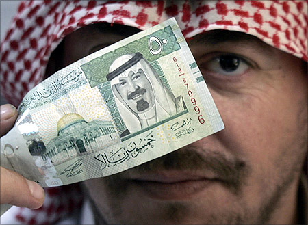A man holds a 50 riyal ($13.3) note, which shows the Dome of the Rock in Jerusalem old city and Saudi's King Abdullah.