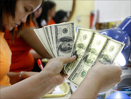 A worker checks $100 bills at a money changer in Manila.