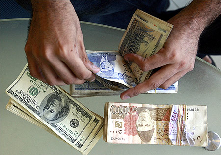A currency dealer counts Pakistani rupees and U.S. dollars at his shop in Karachi.
