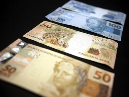 A photo illustration of new Brazilian R$50 and R$100 real currency notes after their launch in Brasilia.
