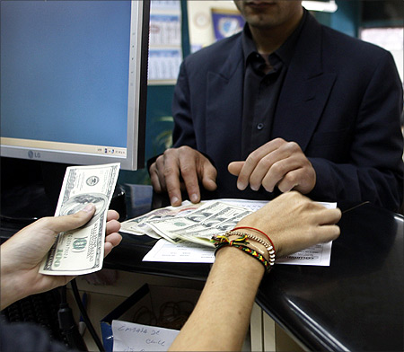 clerk sells dollars at a foreign exchange house in Buenos Aires.