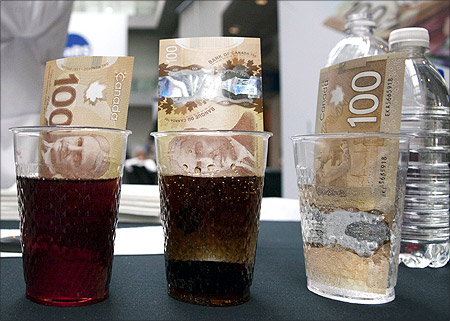 New Canadian 100 dollar bills made of polymer are placed in  glasses of juice, cola and water in Toronto.
