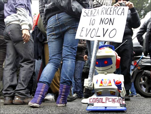 A small toy robot holds up a sign which reads, without research I can't evolve, during a demonstration in Rome.