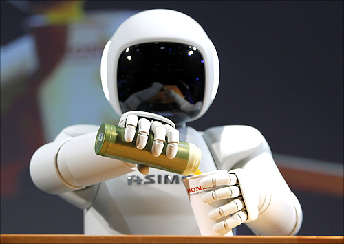 Honda Motor Co's Asimo humanoid robot pours a drink into a cup during a news conference at the 42nd Tokyo Motor Show in Tokyo.