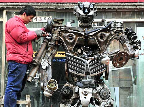 Huang Lianfei, a worker at a metal craft workshop, stands on a ladder as he drills to construct a model robot based on a character from the cartoon Transformers.