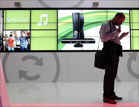 A man checks his messages on his smartphone at the Microsoft booth during the