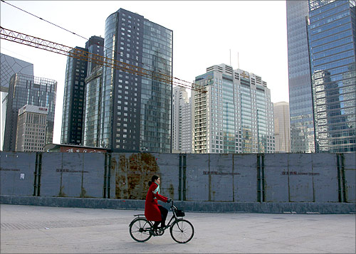 A woman cycles past new buildings and others that are still under construction in central Beijing.