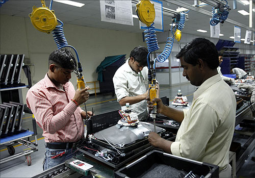 Workers at LG Electronics India Pvt Ltd. assemble television sets inside a factory at Greater Noida.