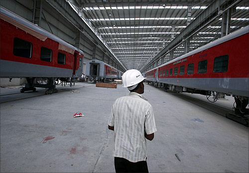 A worker walks past semi-finished rail bogies in a rail coach factory in Uttar Pradesh.