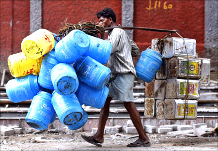 A man carries empty oil containers to a recyclable factory in Kolkata.