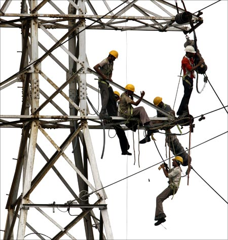 Linemen set up high tension power lines on the outskirts of Ahmedabad