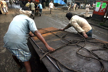 Workers pull a cart laden with metal sheets at an industrial area in Mumbai.