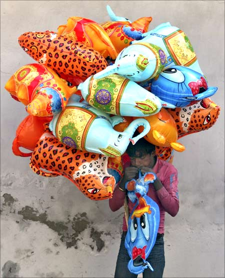 A vendor blows a toy balloon for sale on a street at Noida on the outskirts of New Delhi.