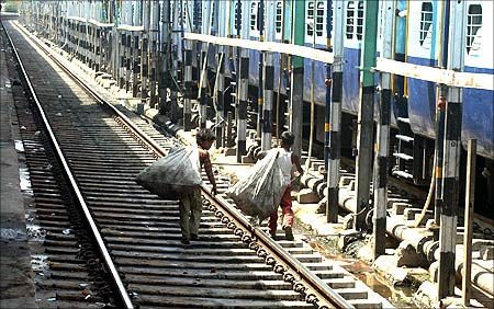 Rag pickers walk along a railway track at the railway station in the northern Indian city of Allahabad.