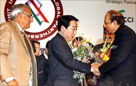 Japan's Prime Minister Yoshihiko Noda (C) shakes hands with Indian Railway Minister Dinesh Trivedi (R).
