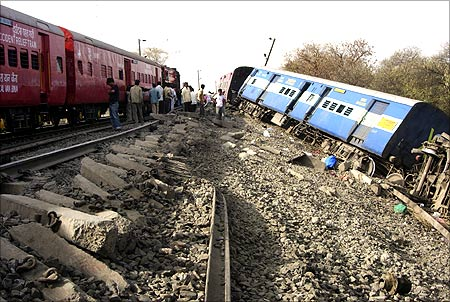 Railway officials and onlookers stand near damaged railway tracks after a passenger train derailed in Vidhisha district.