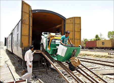 A new auto rickshaw is unloaded from a goods train at a storage facility at Sanand railway station.