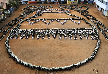 Children arrange themselves into a formation of the Pongal Panai, or an earthen pot, as part of the Pongal festival celebrations in Chennai.