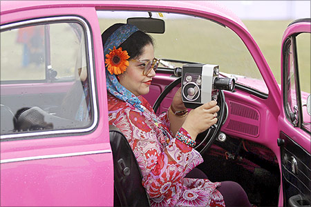 A participant uses a Bolex P4 camera while sitting inside her 1970 Volkswagen 1,285cc classic car in Kolkata.