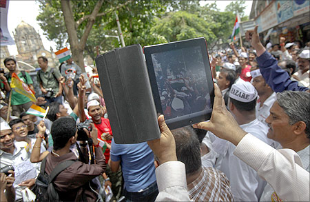A man uses an iPad to shoot video of supporters of veteran Indian social activist Anna Hazare during an anti-government rally in Mumbai.