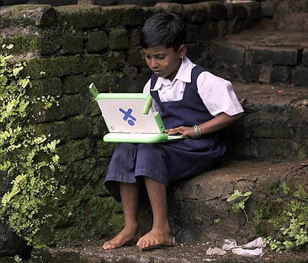 A school girl uses a laptop.
