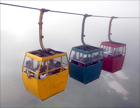 Tourists enjoy their ropeway ride amid a mist of monsoon clouds at the Saputara hill station near Ahmedabad.