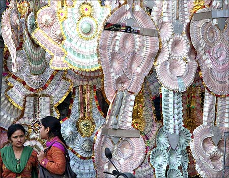 Women stand next to a shop selling garlands made of Indian currency notes in Jammu.