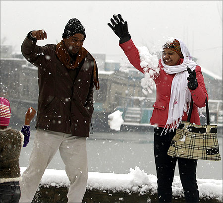A Indian tourist couple playfully tosses snow at each other during the winter season's first snowfall in Srinagar.
