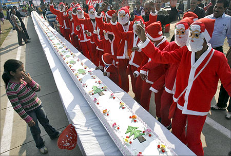 People dressed in Santa Claus costumes dance before they cut a 101-feet (31-metres) long cake as part of Christmas celebrations.