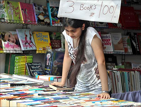 A girl looks at books at a stall selling books.